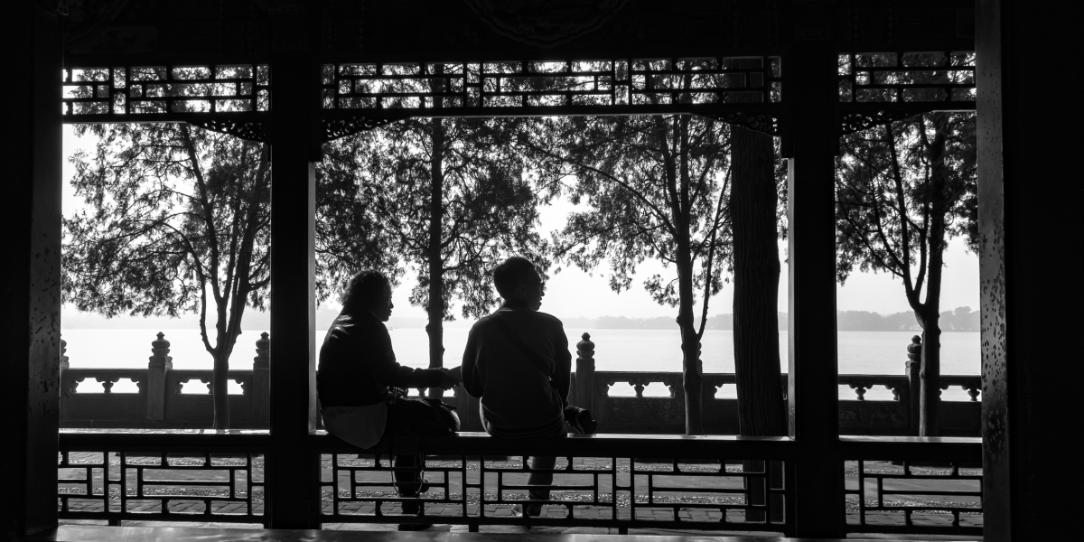 A black and white silhouette of 2 people by the park, Beijing, China.