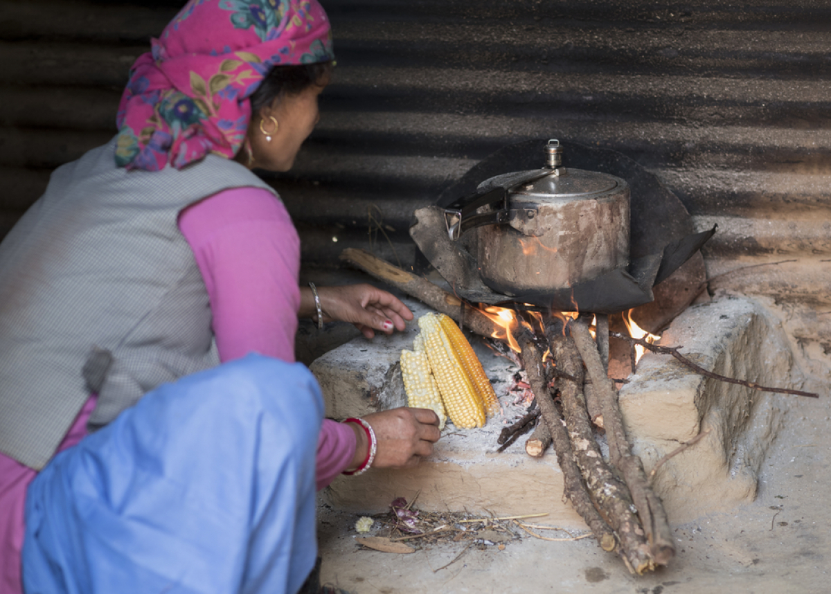 Himachali woman cooking food on wood fire stovein her kitchen, Himachal Pradesh, India.