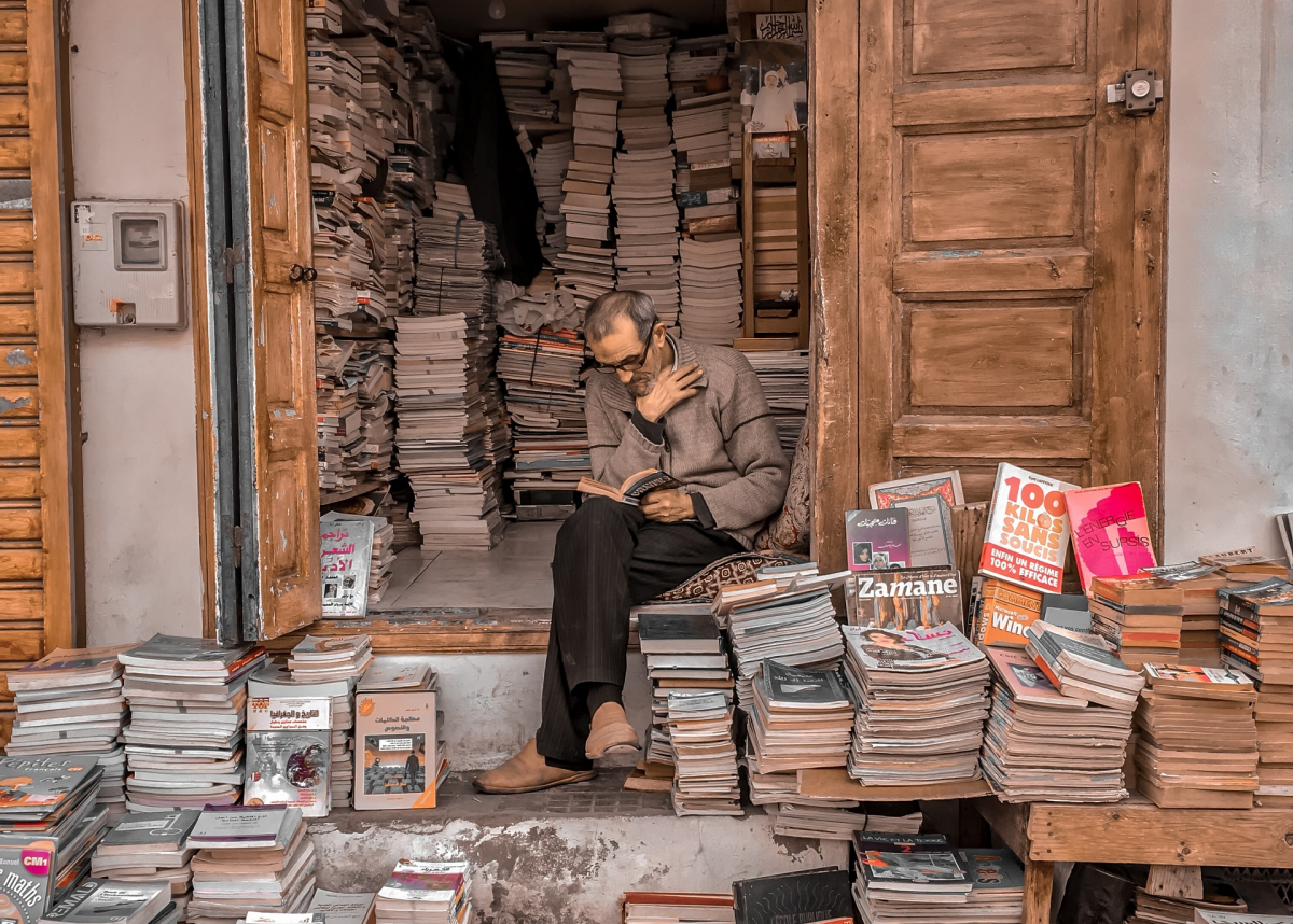 bookseller reading in doorway, Rabat, Morocco